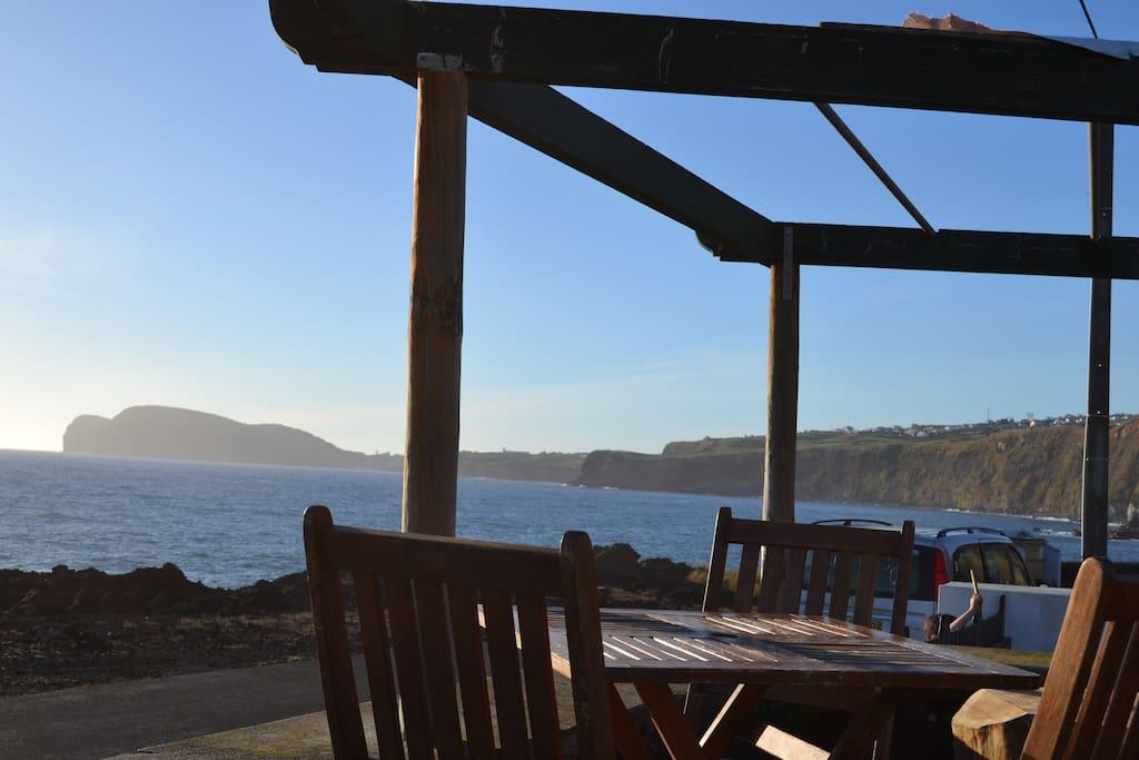 Terraço mesa e cadeiras com vista retalhada da costa, Baía de Angra e Monte Brasil