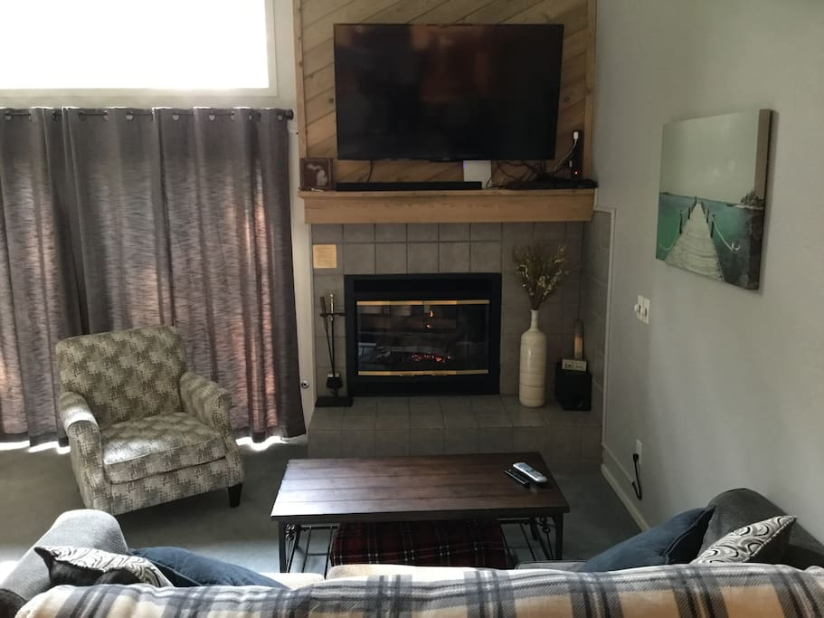 """Living room with 60"""" TV with cable an movie channels"""