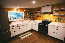 Kitchen with electric stove and basic cookware