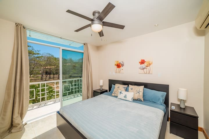 The master bedroom has a comfortable King sized bed, plenty of pillows, air conditioning, a private balcony, and private en suite bathroom