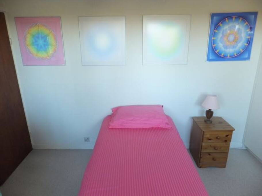Single bed with mandalas above it in downstairs bedroom.