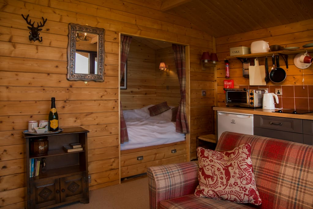 The living room and romantic cabin-styled king-size bed.