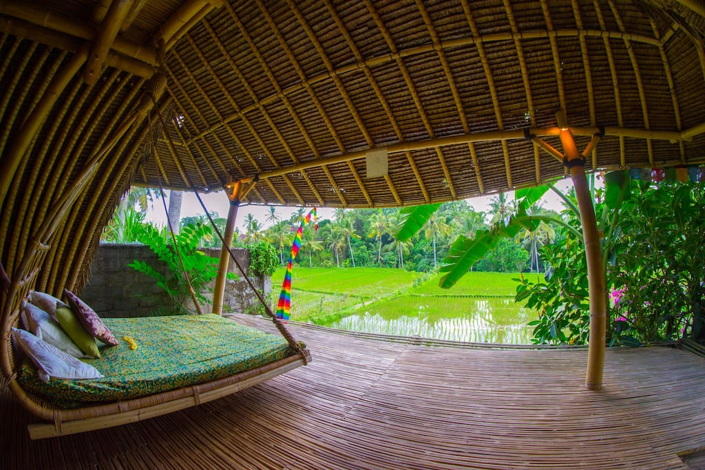 swinging bed for relaxation, with ricefield view.