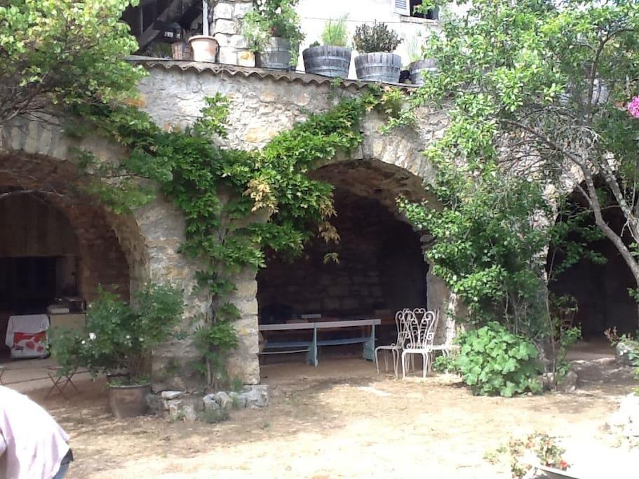 Jardin clos avec espace détente à l'ombre sous les voutes, terrain pétanque, four à pizza