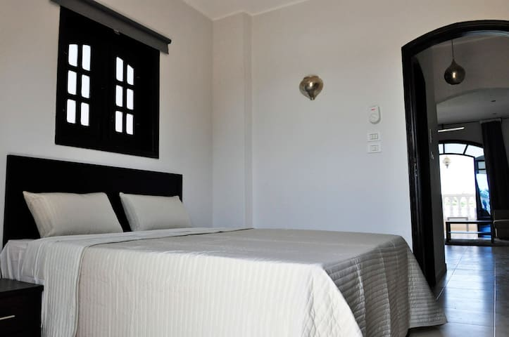 The bedroom has patio doors to the balcony and a window to the side, a bright airy room