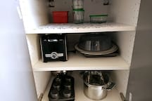 To the left of sink in kitchen cabinet. We have provided pots, baking pans, frying screen and microwave cover. Plus a toaster and a few containers with lids.
