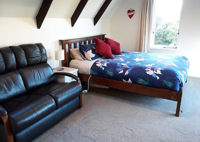 Queen size bed and comfortable leather sofa.