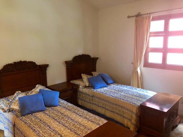 Recámara con dos camas individuales, closet y baño completo privado