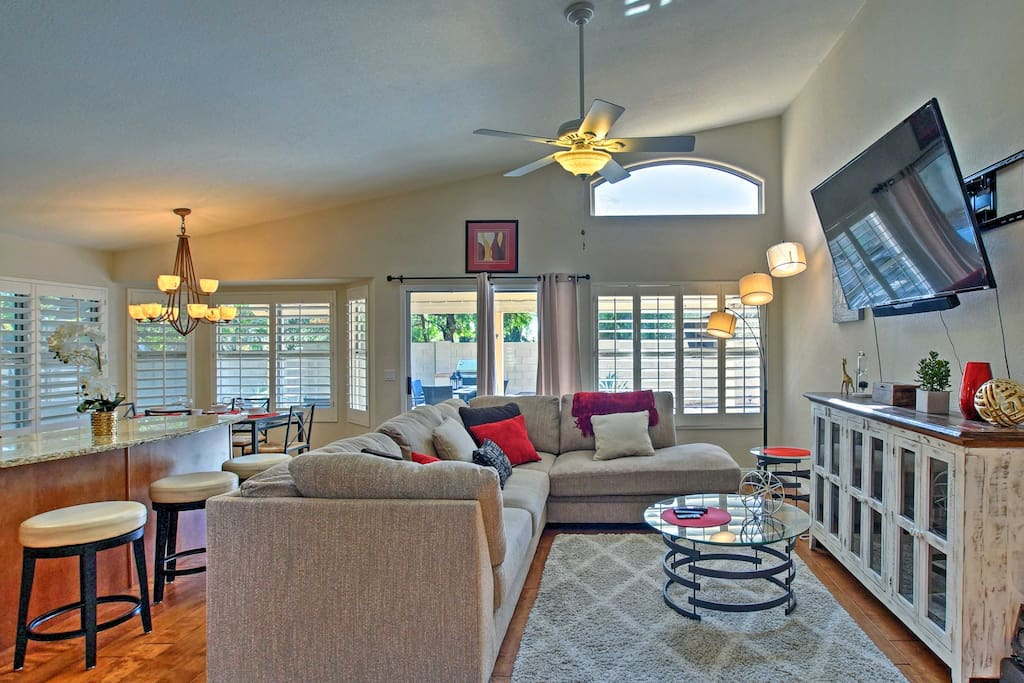 The bright and breezy living area offers a plush L-shaped sofa and flat-screen cable TV.