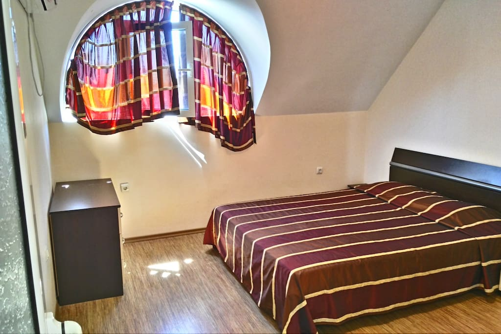 Spacious bedroom with queen size bed and air conditioner. A lot of natural light coming in.