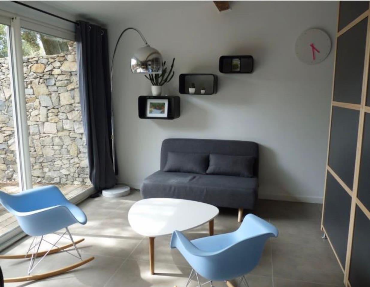 Coin salon avec canapé convertible et fauteuil à bascule. Vue sur la terrasse privative