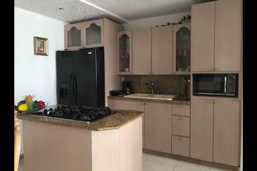 Cocina totalmente equipada con Nevera, Estufa de gas, Horno-Microondas, Cafetera, Tostadora, accesorios de cocina, ollas, Vasos, Platos y cubiertos