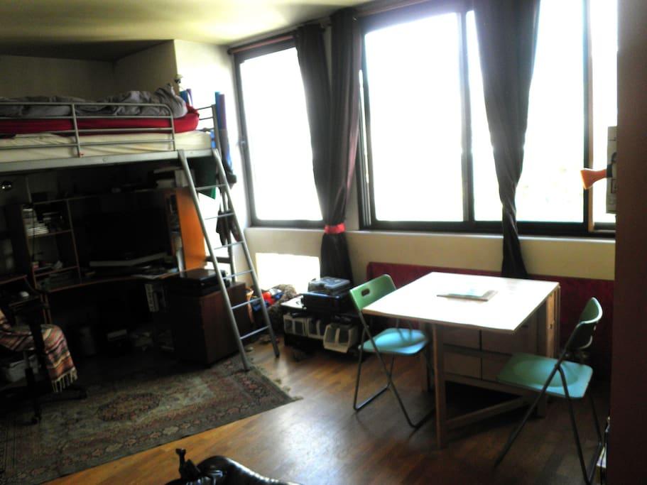 Salon très lumineux. La mezzanine est pour deux personnes. Grand espace bien délimité. La table se déplie pour accueillir 6 convives (chaises pliantes supplémentaires disponibles dans le logement)