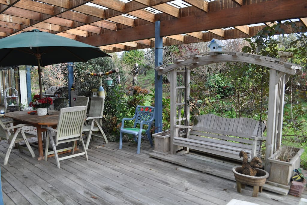 Covered back deck with bbq, smoker, table with chairs, and porch swing.