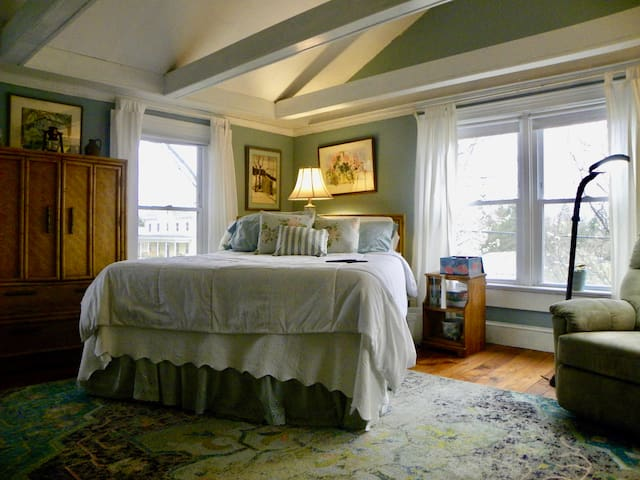 Large Master bedroom with cathedral ceiling, queen bed, air mattress and comfortable reclining Chair.