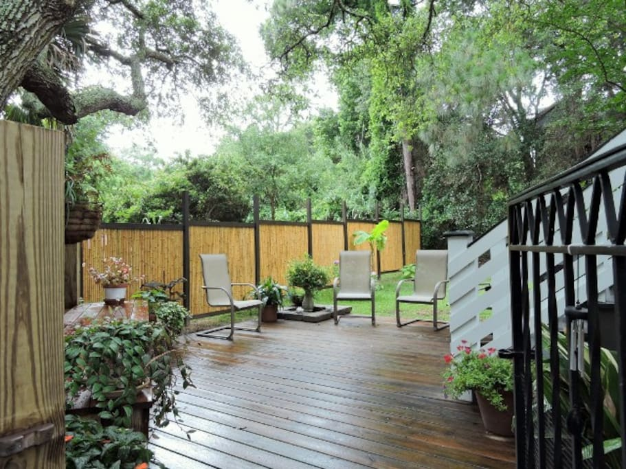 Beautiful outdoor patio with bamboo fencing, gas grill and bench seating