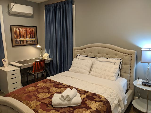 Comfortable queen bed with room-darkening shades, glass night stand and A/C Heater combo unit