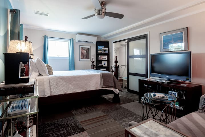 Combined bedroom & living spaces decorated as upscale boutique hotel room