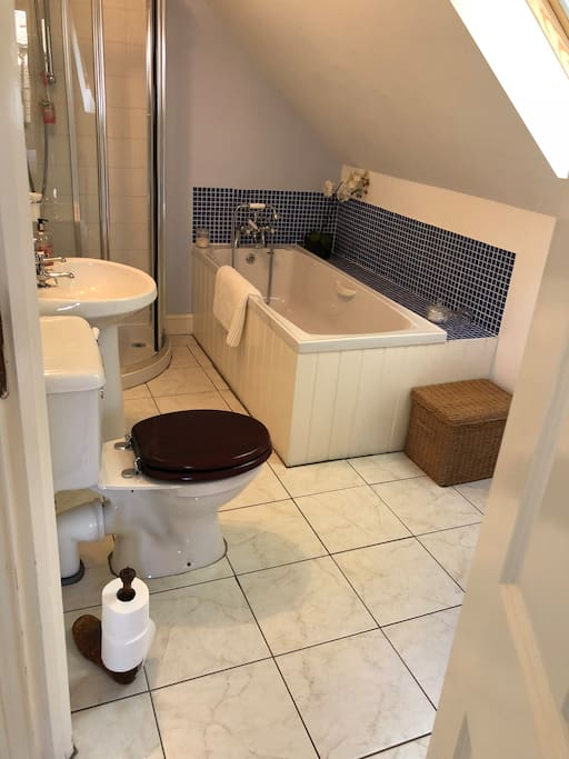 Spacious and clean ensuite offering bath and separate shower. Toiletries are also offered together with a stack of white fluffy towels.