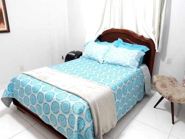 Quarto de casal: cama de casal, poltrona, ar condicionado portátil, roupas de cama e cortina com blackout.