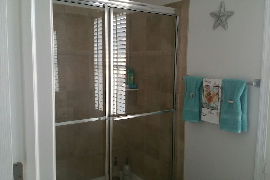 Private bath with ceramic tile shower, vanity and mirror.