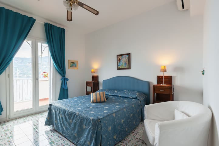 The bedroom has a matrimonial bed, wardrobe, nigthstands, drawers and armchair. There is a French door to enter the terrace. There is  air conditioning and a ceiling fan
