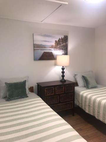 Bedroom with twin beds. This room is shared with laundry facilities.