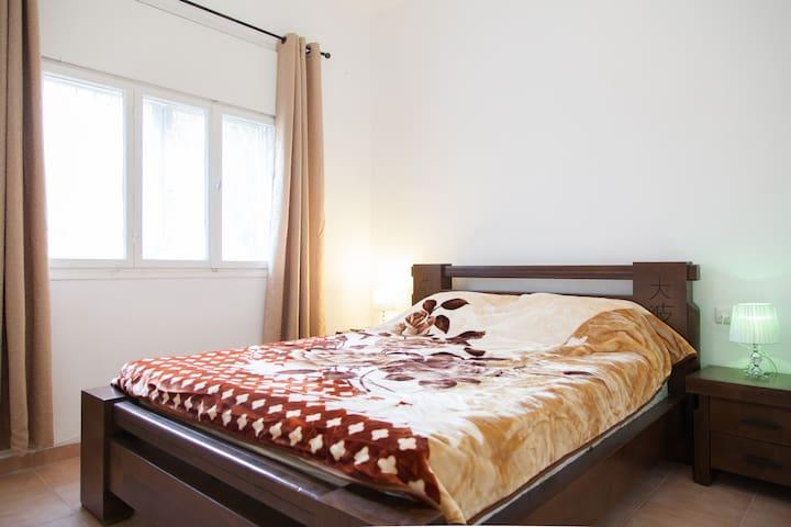 В спальне большое окно и тумбочки,зеркало