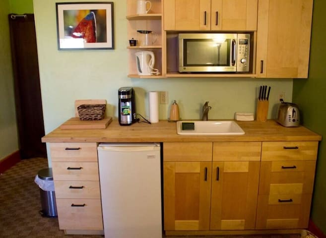 The kitchen has a small refrigerator, a microwave/toaster oven, coffee maker and electric wok.