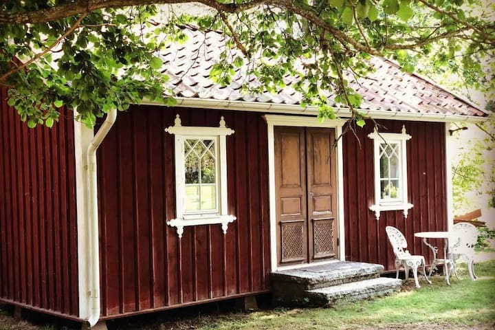 Charmigt gårdshus i lummig omgivning på hästgård
