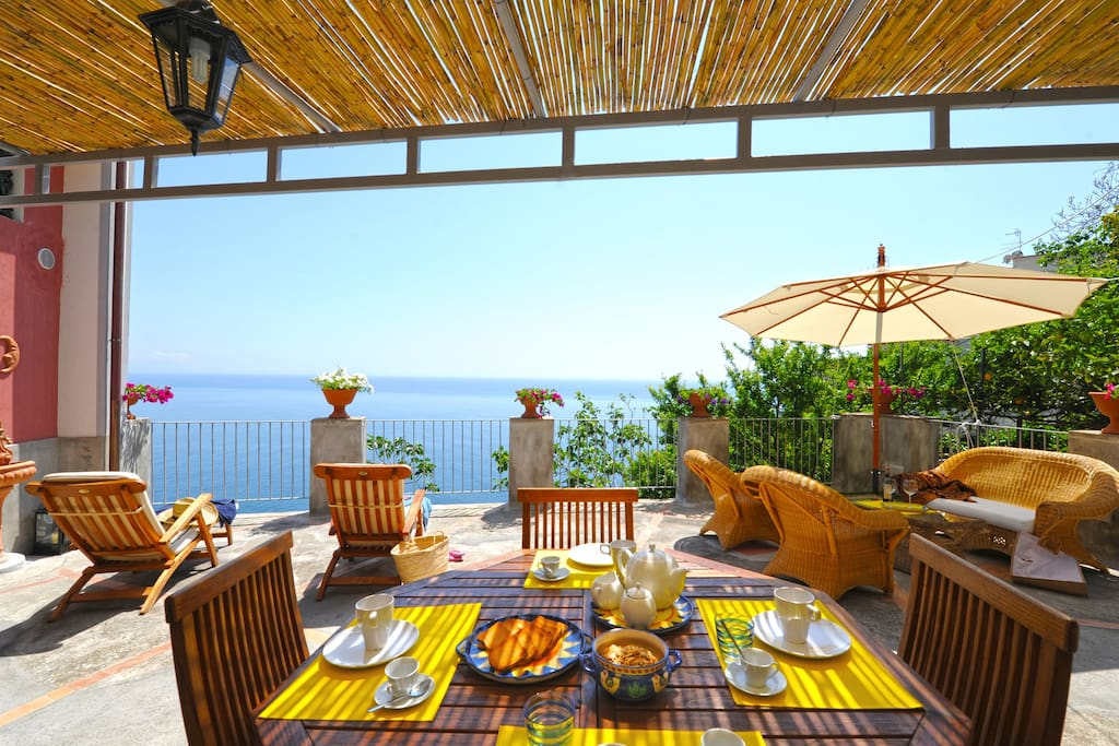 Large terrace surrounded by greenery with wicker sofas, sun beds, sea view