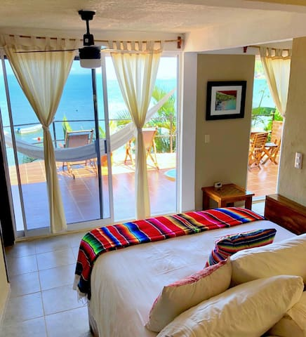 The view of the ocean from the queen bed through the over-sized sliding glass doors.