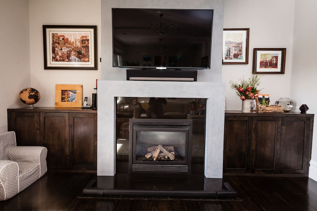 "Open living room, with a 55"" smart TV mounted over the fireplace"