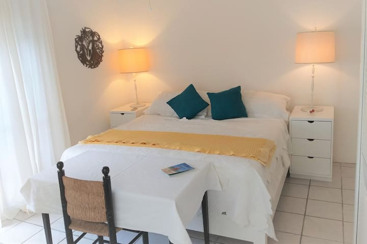 The room features a King Sized hand made wooden bed,  white cotton drapes and linens, bespoke bedside tables with charging strips, pretty lamps, Caribbean Art and a writers desk. Choice of ceiling fan or A/C (or both) to keep you cool.
