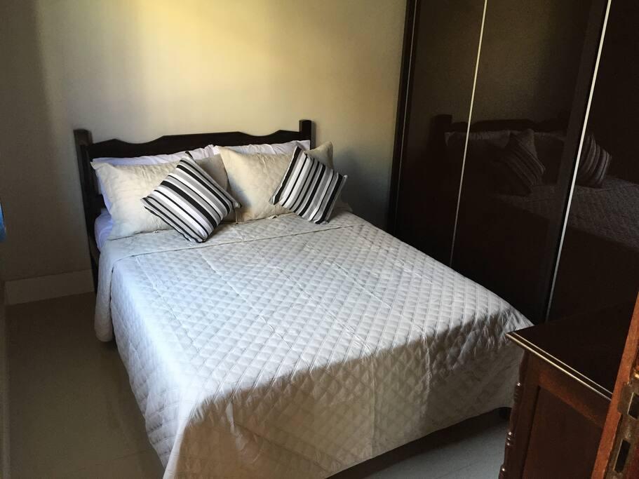 Cama de casal, cômoda e armário.