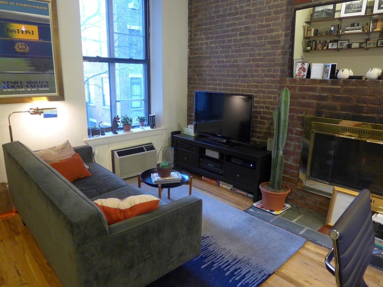 Cozy living room with exposed brick wall and oversize window