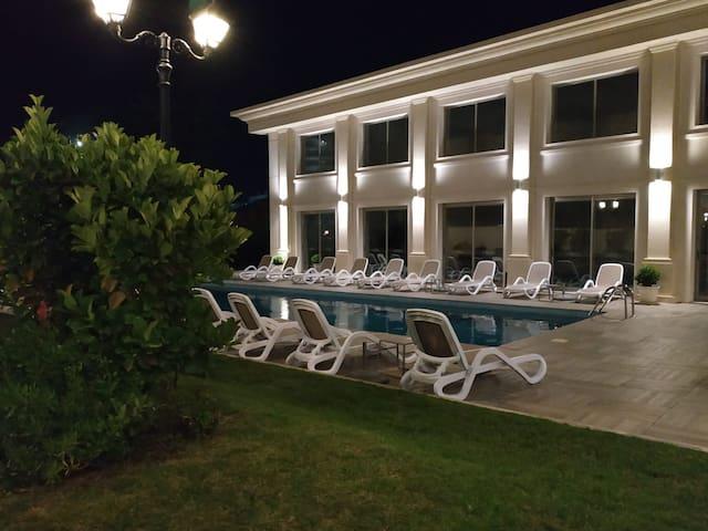 Vista nocturna de la piscina exterior climatizada.