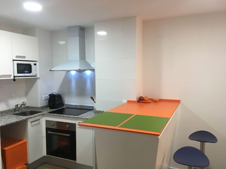 Cocina equipada con frigorífico, cafetera, microondas, horno, lavadora, vitrocerámica y resto de utensilios.