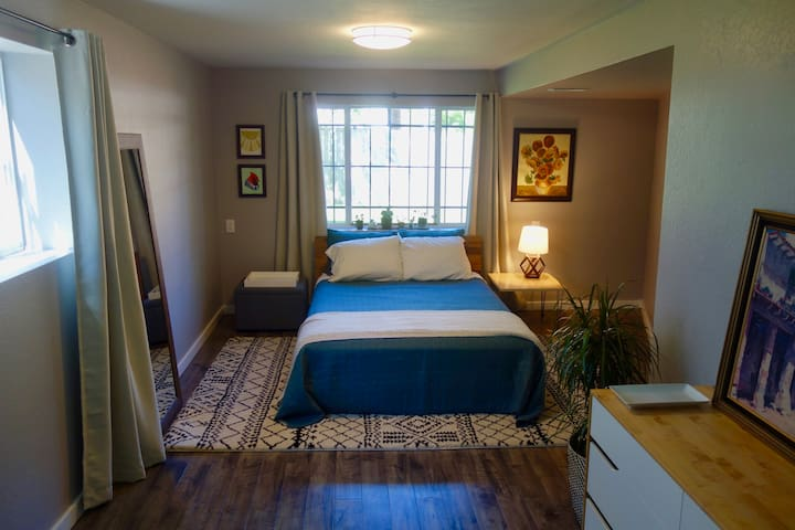 A comfy place to relax: the main bedroom with a queen bed and great light.