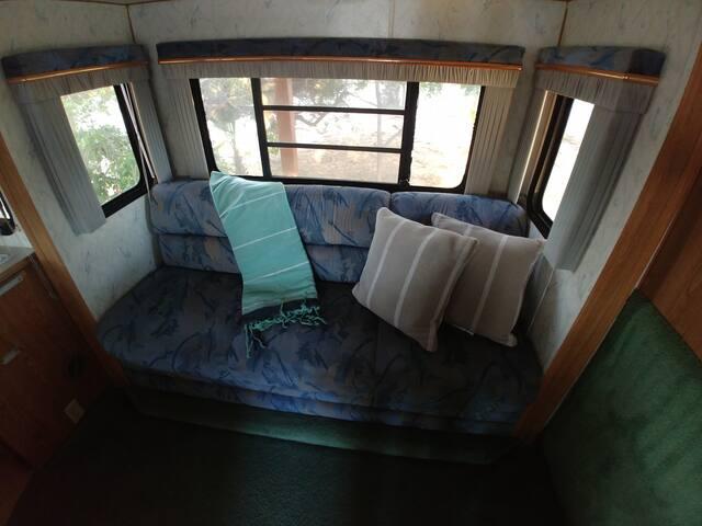Sofá cama camper 2. Individual con sábanas y almohadas. Ventanas con persianas.