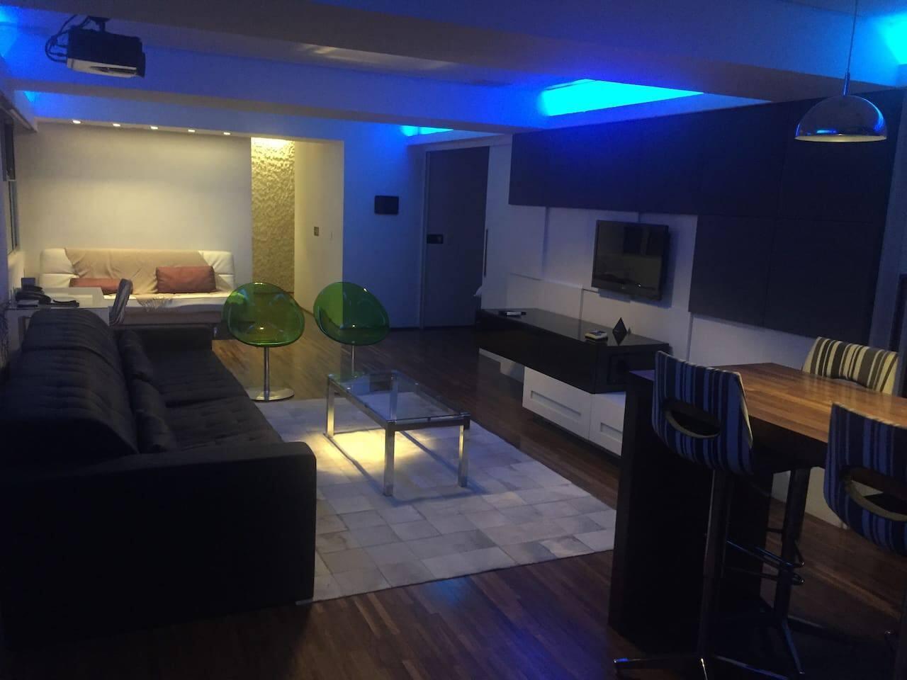 Ampla sala com TV, mesa com 6 lugares, sofá de 4 lugares, sofá cama ao fundo (modo noturno)