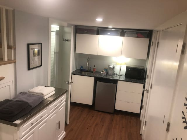 This is the new kitchenette, which features a sink, refrigerator, microwave, and Keurig. You can also find additional blankets, linens, towels, and amenities here.