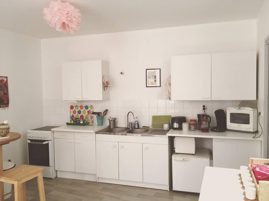 Cuisine ouverte sur le salon toute équipée : four, plaques de cuisson électriques, micro onde, machine à café, bouilloire, ...
