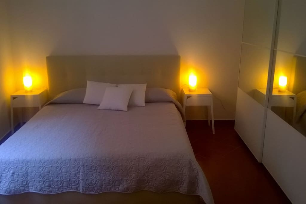 Il letto matrimoniale e l'ampio armadio con specchio della camera da letto matrimoniale