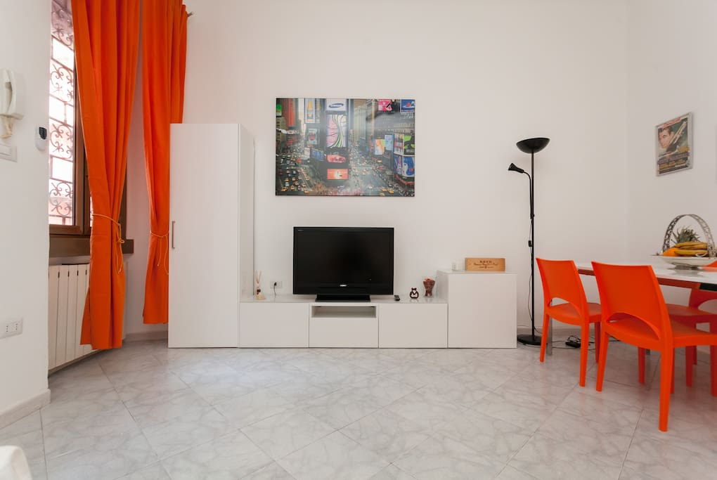 The living room: sofa, TV & the dining table