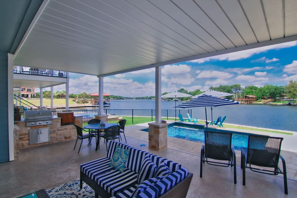 Covered patio with outdoor gas grill, sofas, chaise lounges, table with seating for 4, bar cart, child sized table and chairs