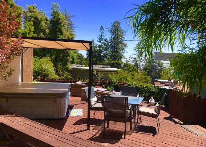 Deck area with hot tub, dining room table and outdoor couches surrounded by greenery and beautiful bay views!