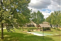 Large outdoor common area with basketball court, volleyball, outdoor pavilion,  pool, and shuffleboard.