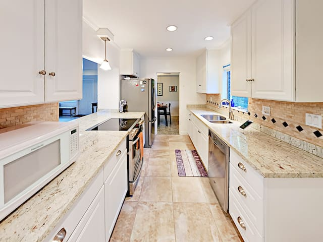 The beautifully remodeled kitchen features granite countertops and freshly tiled floors.