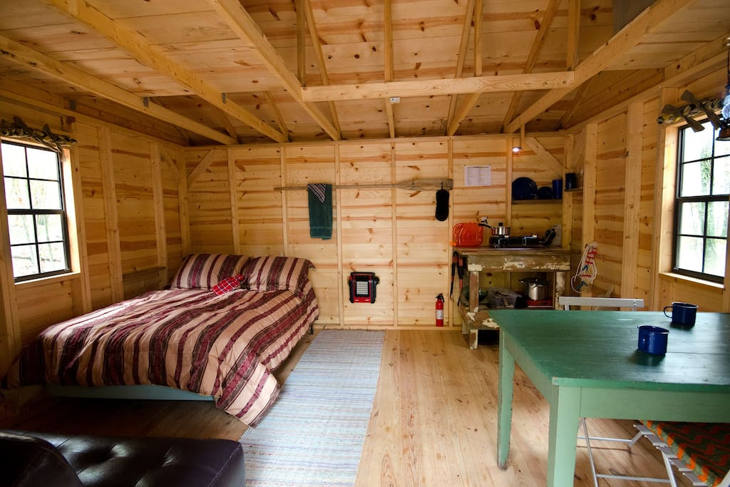 Hut interior.  Double bed, dining table, kitchen area.  Also a couch that folds to another double bed.